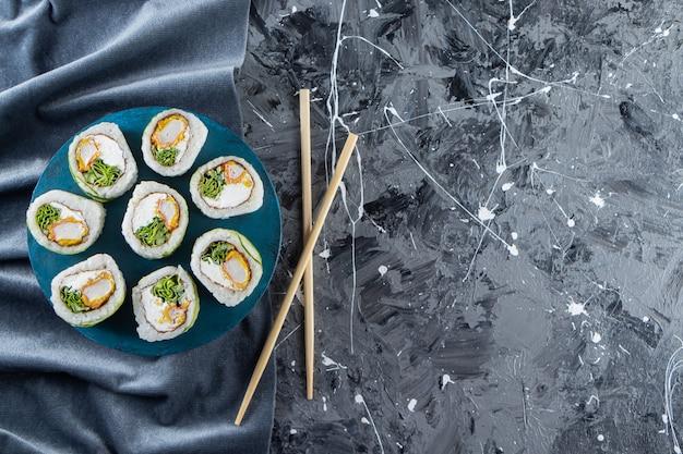 Rolos de sushi de dragão verde colocados no quadro azul.