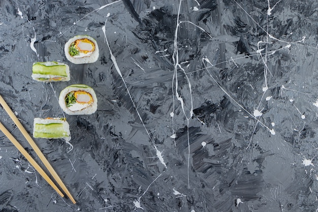 Rolos de sushi de dragão verde colocados sobre fundo de mármore.