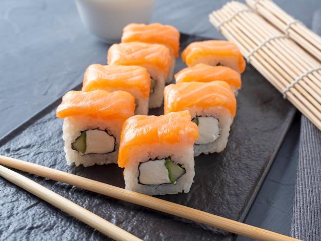 Rolos de sushi de filadélfia em um suporte de placa texturizado preto sobre um fundo cinza. há pauzinhos de bambu nas proximidades. vista lateral, culinária japonesa