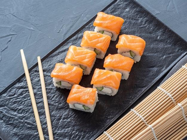 Rolos de sushi de filadélfia em um suporte de placa texturizado preto sobre um fundo cinza. há pauzinhos de bambu nas proximidades. vista superior, configuração plana. culinária japonesa