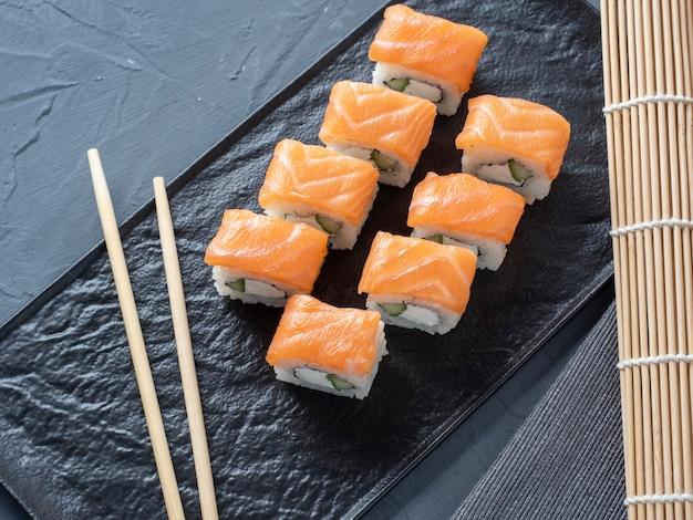 Rolos de sushi de filadélfia em um suporte de placa texturizado preto sobre um fundo cinza. vista superior, configuração plana