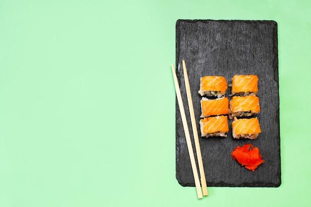 Rolos de sushi de peixe com salmão, wasabi e pauzinhos na tábua de servir de corte preto no verde. frutos do mar
