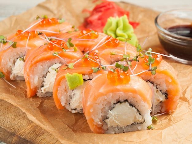 Rolos de sushi de salmão da filadélfia com molho de soja.