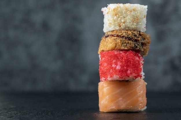 Rolos de sushi de salmão isolados na mesa preta.
