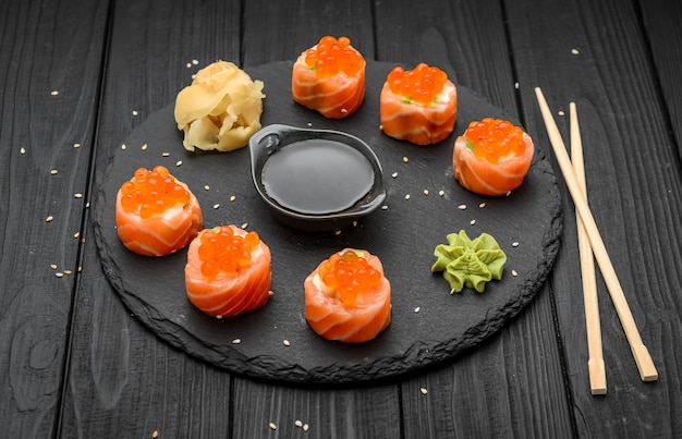 Rolos de sushi de salmão no preto.