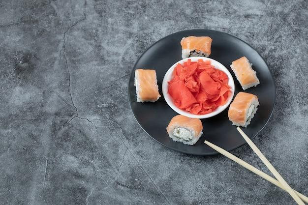 Rolos de sushi de salmão servidos com gengibre vermelho em um prato preto.