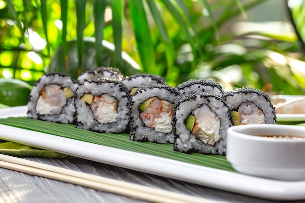 Rolos de sushi de vista lateral com camarão com molho de soja em um prato