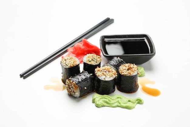Rolos de sushi delicioso, molhos e pauzinhos na superfície branca