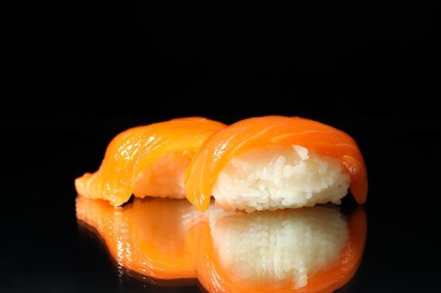 Rolos de sushi delicioso no espelho preto. comida japonesa