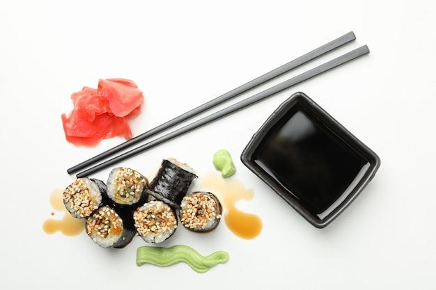 Rolos de sushi delicioso, soja e pauzinhos na superfície branca