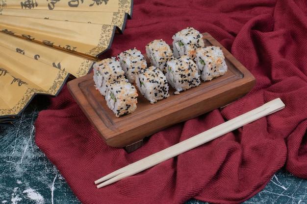 Rolos de sushi do alasca servidos em travessa de madeira com pauzinhos e leque japonês.