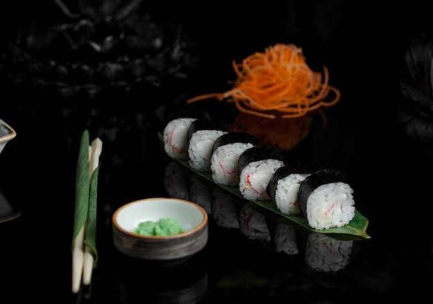 Rolos de sushi e abacate picado em uma mesa preta