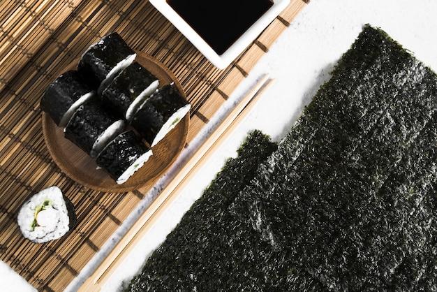 Rolos de sushi e molho de soja na esteira de bambu perto de algas