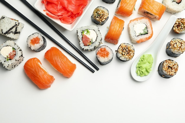 Rolos de sushi e pauzinhos na superfície branca. comida japonesa