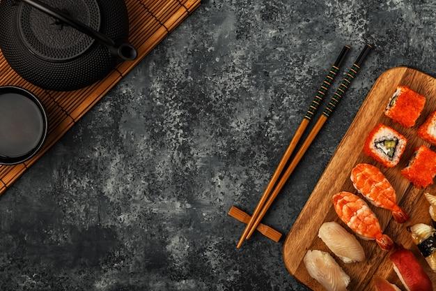 Rolos de sushi e sushi em placa de madeira, vista superior