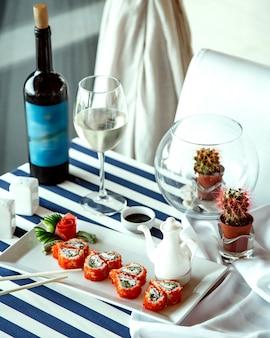 Rolos de sushi e um copo de vinho branco