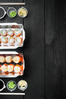Rolos de sushi em conjunto de recipiente para viagem, no fundo preto da mesa de madeira, vista de cima plana, com copyspace e espaço para texto