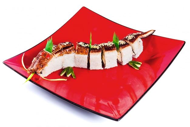 Rolos de sushi em um prato vermelho sobre fundo branco isolado (dragão de unagi). cozinha japonesa tradicional