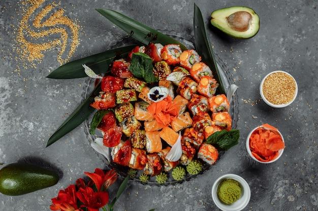 Rolos de sushi em uma bandeja de cristal. rolls: filadélfia, dragão verde, havaí, dragão vermelho, ebi shake