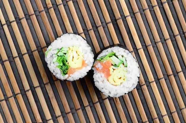 Rolos de sushi encontra-se em um tapete de serwing de palha de bambu