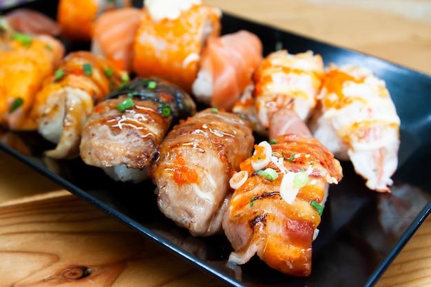 Rolos de sushi fresco no prato preto, saudável e delicioso menu asiático tradicional