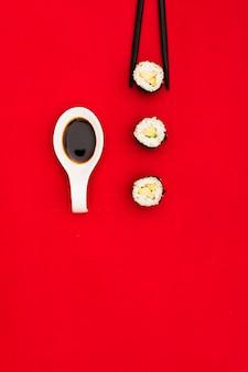 Rolos de sushi frescos; molho de soja na colher e pauzinhos pretos na superfície vermelho escuro