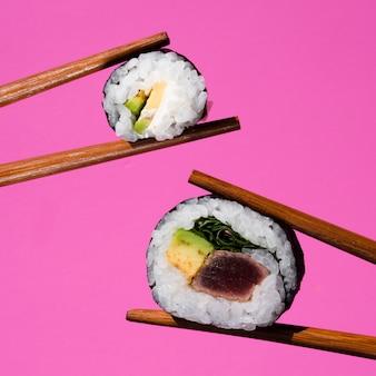 Rolos de sushi holded por pauzinhos em um fundo rosa