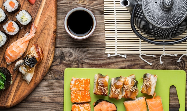 Rolos de sushi japonês com molho de soja e bule