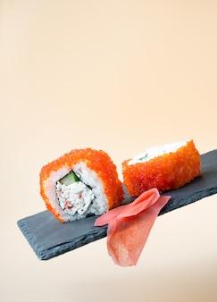 Rolos de sushi japonês fresco tradicional e gengibre em placa preta flutuante sobre fundo bege claro