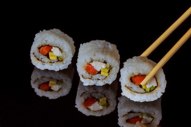 Rolos de sushi japonês fresco tradicional em fundo preto