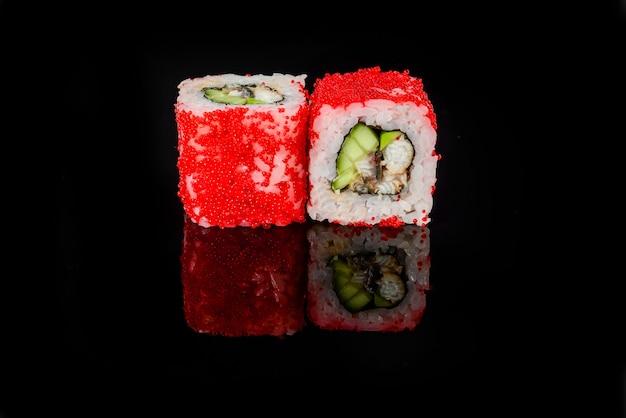 Rolos de sushi japonês fresco tradicional em um fundo preto