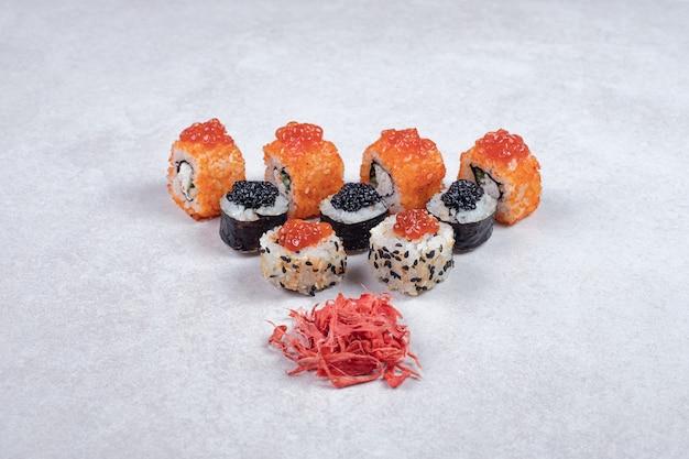 Rolos de sushi maki, alasca e califórnia em fundo branco com gengibre em conserva.