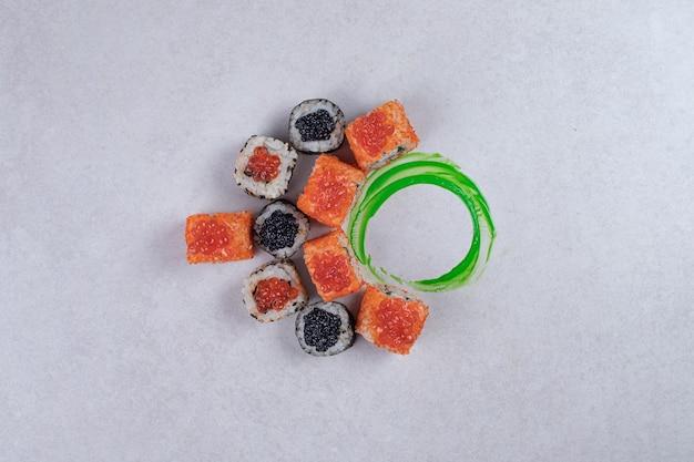 Rolos de sushi maki, alaska e califórnia em fundo branco com anel de plástico verde.