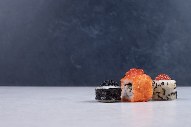 Rolos de sushi maki, alaska e califórnia na mesa branca.