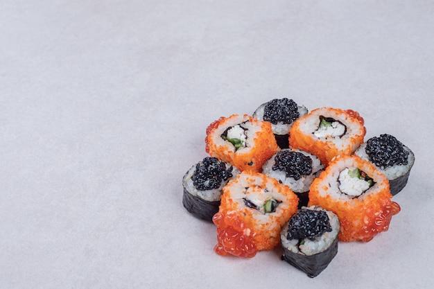 Rolos de sushi maki e califórnia em fundo branco.