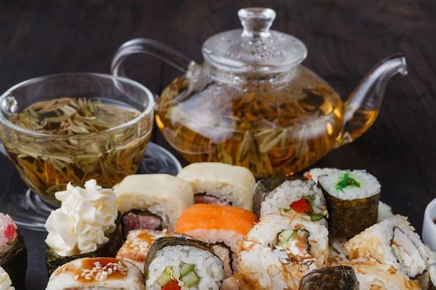 Rolos de sushi maki e nigiri frescos e deliciosos e copo de chá verde
