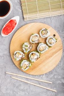 Rolos de sushi maki japonês com cebola verde na placa de madeira no fundo cinza de concreto. vista superior, close-up.