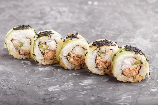 Rolos de sushi maki japonês com queijo de gergelim preto de pepino de atum em fundo preto de concreto