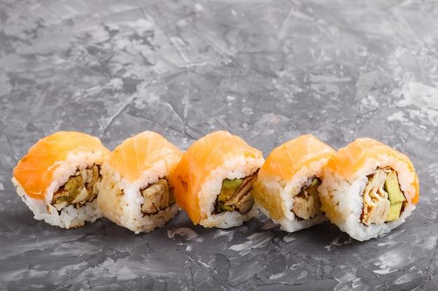 Rolos de sushi maki japonês com salmão, abacate e omelete em fundo preto de concreto. vista lateral.