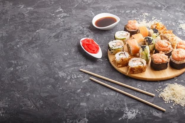 Rolos de sushi maki japonês misturado com pauzinhos, gengibre, molho de soja, arroz em fundo preto de concreto, vista lateral.