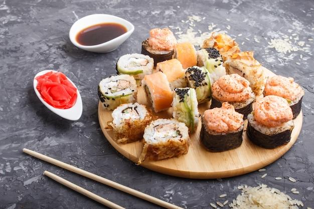 Rolos de sushi maki japonês misturado com pauzinhos, gengibre, molho de soja, arroz na superfície de concreto preta, vista lateral.