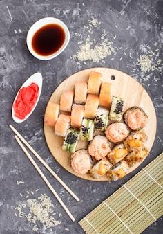Rolos de sushi maki japonês misturado com pauzinhos, gengibre, molho de soja, arroz, vista superior.