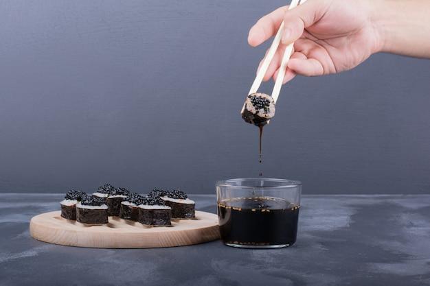 Rolos de sushi maki na placa de madeira com pauzinhos, gengibre em conserva e molho de soja.