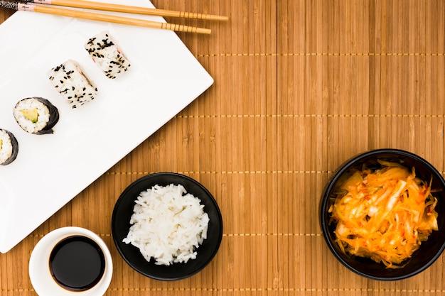 Rolos de sushi; molho de soja; arroz cozido no vapor e salada sobre placemat