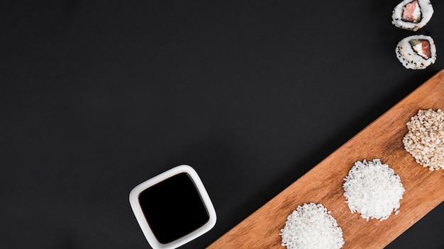 Rolos de sushi; molho de soja com arroz cru branco e marrom no fundo preto
