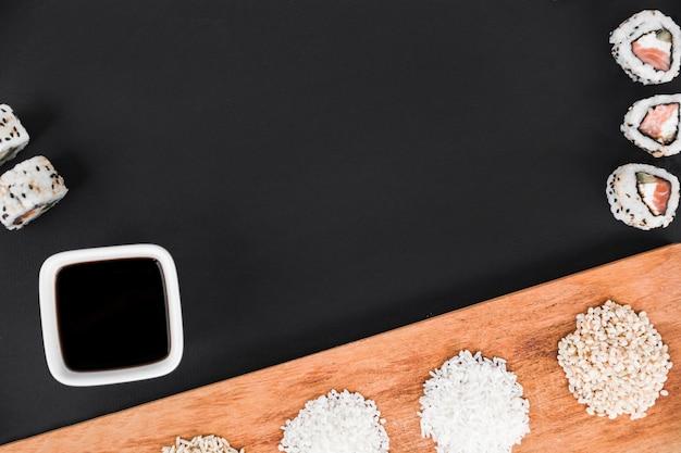 Rolos de sushi; molho de soja e arroz cru na bandeja de madeira sobre o fundo preto