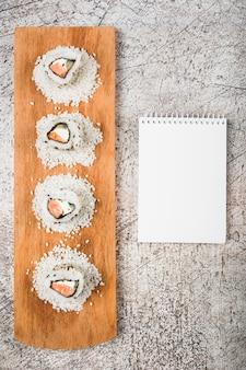 Rolos de sushi na bandeja de madeira com o bloco de notas espiral em branco sobre fundo rústico