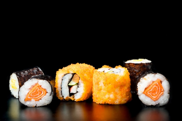 Rolos de sushi no fundo preto, alimento japonês.