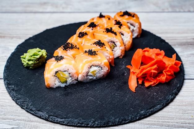 Rolos de sushi no prato de pedra preto. pizza deliciosa servida na placa de madeira