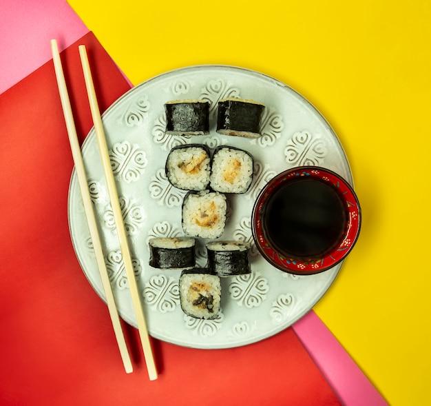 Rolos de sushi nori com enguia servidos com molho de soja